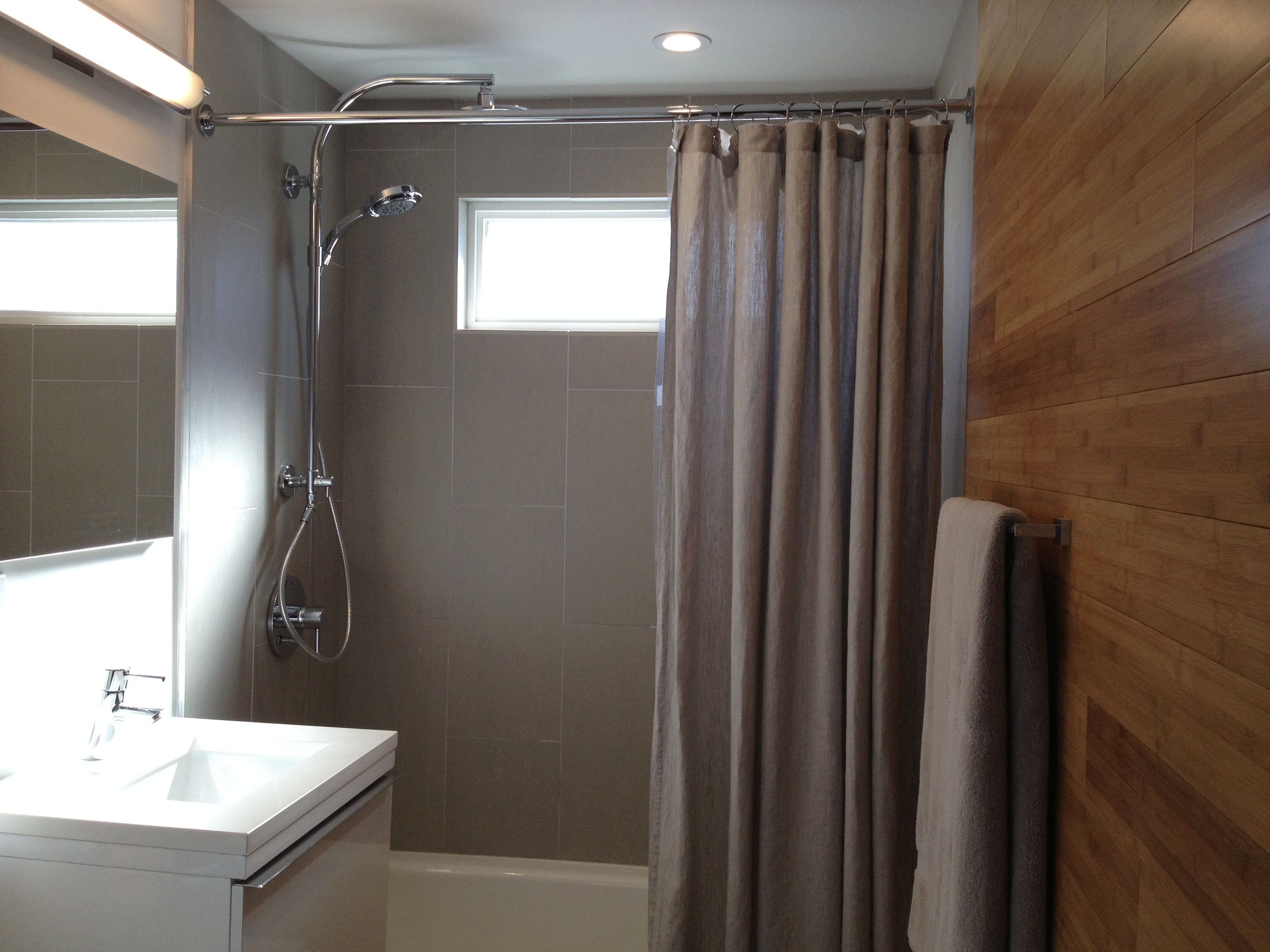 Wall hung vanity & tile installed vertically create visual space.